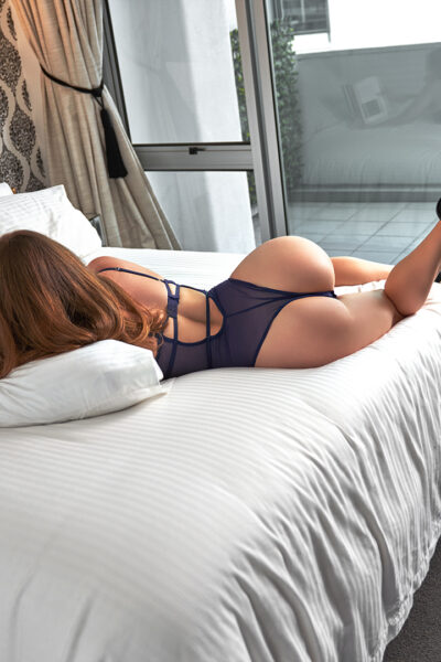 Zara Marlow lying on her front on a bed, leaning up on elbows, reading a book, one leg is off the side of the bed, the other bent up, foot in air. Zara wears a dark blue bodysuit and black heels and has long brown hair. NZ Pleasures.