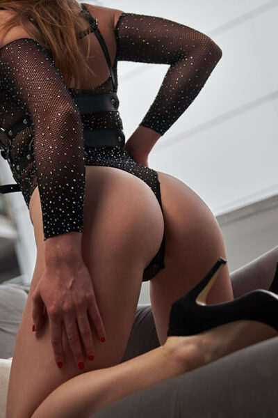 Zara Marlow kneeling on a couch, one hand on side of thigh, the other on hip, back partially to camera. Zara wears a black bodysuit and black heels and has long brown hair. NZ Pleasures.