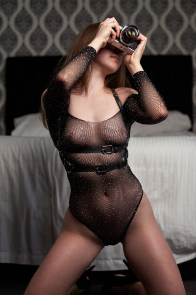 Zara Marlow kneeling on the floor at the foot of a bed, knees wide apart, holding a camera up to her face. Zara wears a black bodysuit with a body harness and heels. Zara has long brown hair. NZ Pleasures.