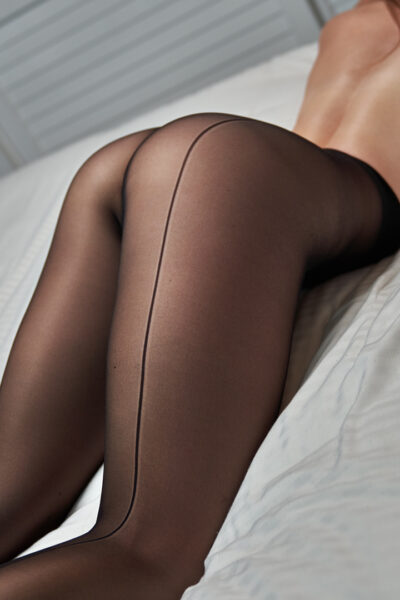 Zara Marlow lying on her front on a bed, back arched. Zara wears black pantyhose and has long brown hair. NZ Pleasures.