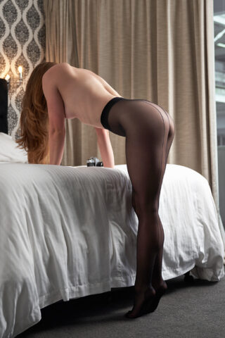 Zara Marlow leaning over the end of a bed, hands on the bed, standing on tip toes, hair falling over her face. Zara wears black pantyhose and has long brown hair. Photo is taken side on. NZ Pleasures.