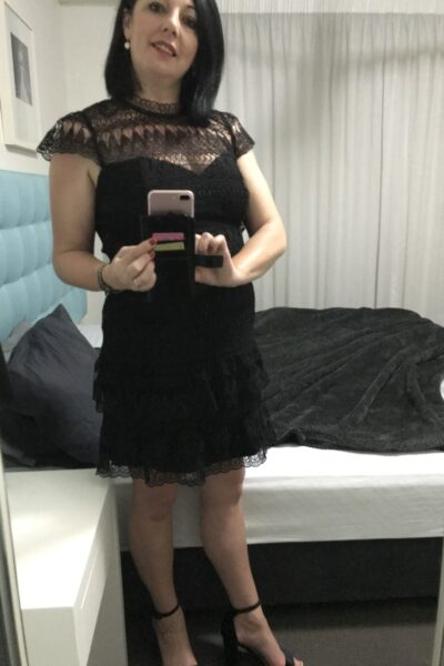 Nicky Love taking a selfie in the mirror, smiling, head titled slightly to one side. Nicky wears a black short sleeve dress, black heels and has shoulder length black hair. NZ Pleasures.