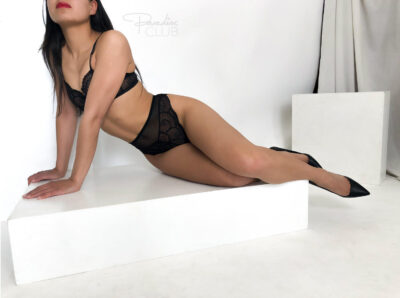 Eve sitting with knees bent up, leaning on hands to one side, head titled back. Eve wears black lingerie with black heels and has long black hair. NZ Pleasures.