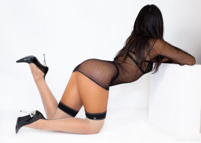 Eve kneeling on the floor, leaning forward on elbows on a white cube in front of her, head turned away from camera, one foot in the air. Eve wears a black fishnet long sleeve mini dress with white stockings with black tops and black and silver heels. Eve has long black hair. NZ Pleasures.