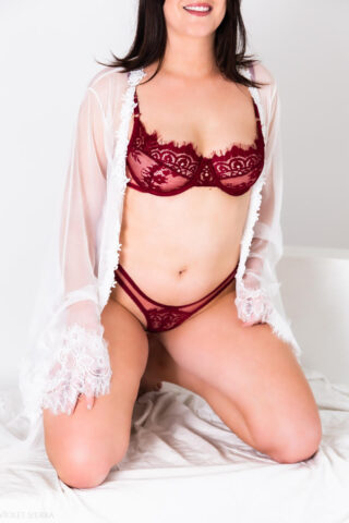 Imogen kneeling, knees apart, hands on tops of thighs, smiling at the camera. Imogen wears dark red lingerie and a white lace kimono that is undone. Imogen has medium length black hair. NZ Pleasures.