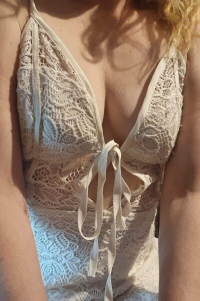 Roxy from shoulders to hips, hands on thighs. Roxy wears a white lace dress and has blonde hair. NZ Pleasures.