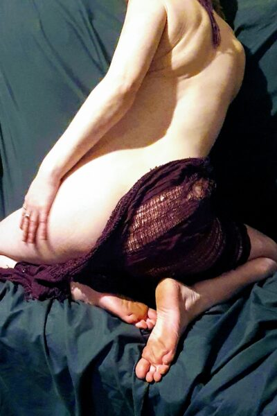 Roxy kneeling on knees on a couch, knees wide apart, back to camera, one hand on thigh, head turned back towards camera. Roxy is naked except for a back cloth that falls over one side of buttocks. NZ Pleasures.