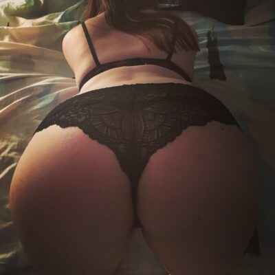 Anna bending over a bed, buttocks to camera. Anna wears black lingerie and has long dark hair. NZ Pleasures.
