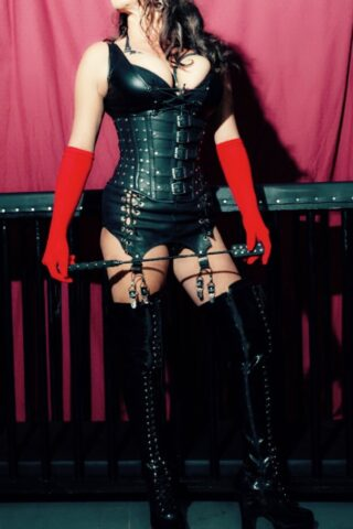 Mistress Dior posing with legs apart, holding a crop infront of her with both hands, head turned to one side. Mistress Dior wears a black leather corset with black leather bra, red gloves and black over the knee boots. NZ Pleasures.