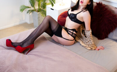 Pepper reclining on a bed, leaning back on hands, knees bent up, her mouth open. Pepper wears black lingerie, a beige and black poker dot blouse that is off her shoulders, black thigh high stockings, red stilettos and has long black hair. NZ Pleasures.