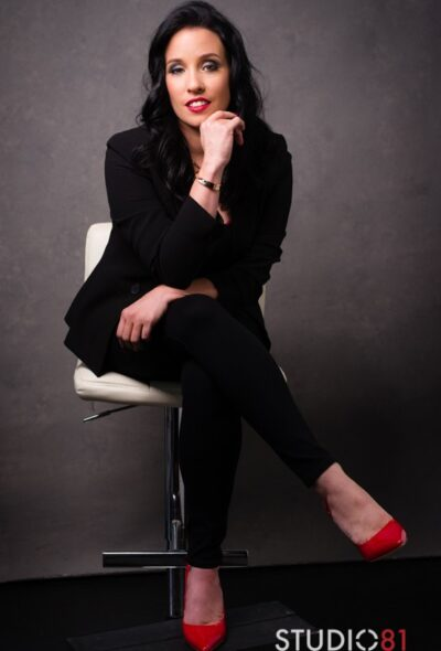 Mistress Vivian sitting cross legged on a white stool, one arm resting across lap, the other under her chin. Mistress Vivian wears a black suit with red heels and has long black hair. NZ Pleasures.
