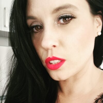 Portrait photo of Mistress Vivian, her long black hair pulled around to one side, wearing red lipstick. NZ pleasures.