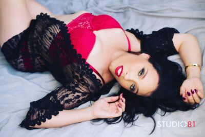 Mistress Vivian lying on her back, knees bent up, head to one side looking up at camera, one arm above head, the other up by her face. Mistress Vivian wears a red bustier and black lace kimono that is undone. Mistress Vivian has long black hair. NZ Pleasures.