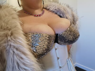 Dita Lovegood posing partially side on to camera, wearing a black and gold sequin bra, a white corset and light grey fur jacket. NZ Pleasures.