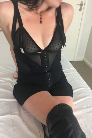 Imogen sitting with legs extended out infront of her, one ontop of the other, leaning on hands behind her, head turned to one side. Imogen wears black teddy and black over the knee boots. NZ Pleasures.
