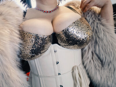 Dita Lovegood posing with one hand on top of shoulder. Dita wears a black and gold sequin bra, a cream corset and light grey fur jacket. NZ Pleasures.