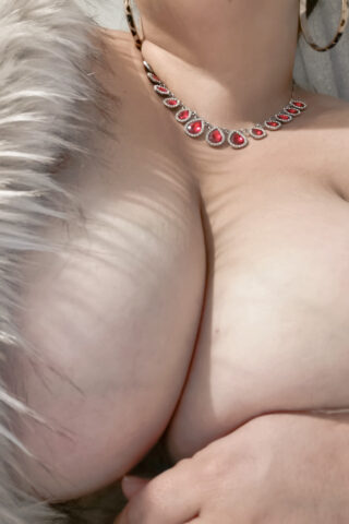 Close up photo of Dita Lovegood's breasts. Dita wears a light grey fur coat that is undone. NZ Pleasures.