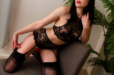 Pepper kneeling side on a chair, knees apart, leaning on one elbow on the back of the chair, her other hand on her thigh. Pepper wears black lace lingerie with black thigh high stockings and has long black hair. NZ Pleasures.