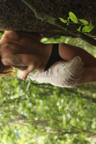 Ana leaning against a tree in the bush, back to camera, one leg in front of the other, holding a large white feather that curls around her body to cover one buttock. Ana wears black panties and has brown hair. NZ Pleasures.