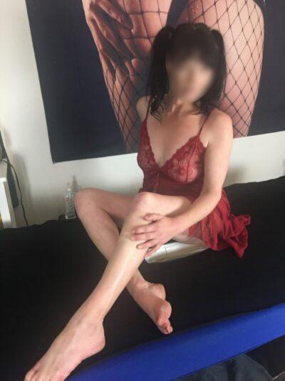 Imogen sitting on a massage table, legs partly crossed, hand on side of knee. Imogen has black hair and wears a dark red teddy. NZ Pleasures.