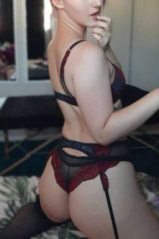 Lana Amator kneeling on a bed, knees wide apart, partially side on to camera, turning around to look at camera, fingers on chin, the other arm in mid air. Lana wears black and maroon lingerie with suspender belt and black thigh high stockings. NZ Pleasures.