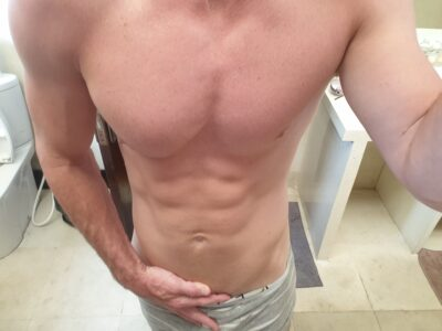 Seth taking a selfie from chest down, hand in top of pants. Seth is topless and wears light brown pants. NZ Pleasures.