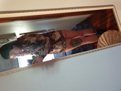 Laura Palmer taking a selfie in the mirror, turning back towards mirror. Laura wears a long sleeve mini dress, glasses and has brown hair and a tattoo on the back of one thigh. NZ Pleasures.