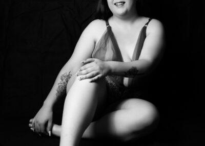 Black and white photo of Natalie Vaughn sitting with one leg bent up, the other tucked under the leg, one hand on front of knee, the other holding the foot that is tucked under, smiling. Natalie wears a bodysuit and has a tattoo on one arm. NZ Pleasures.
