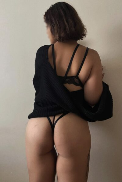 Solana standing with back to camera, hands on wall in front of her, head turned to one side. Solana wears black lingerie and a black cardigan which is off one shoulder. NZ Pleasures.