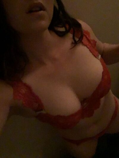 Kali taking a selfie from above while wearing red lingerie. Kali has long brown hair. NZ Pleasures.