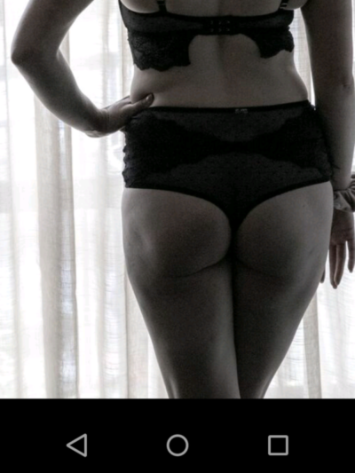 Black and white photo of Kali standing with back to camera, one leg in front of the other, one hand on hip. Kali wears black lingerie. NZ Pleasures.