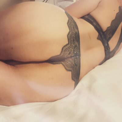 Close up of Danielle's buttocks while lying on her side. Danielle wears black lace lingerie. NZ Pleasures.