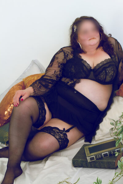 Addison Lane reclining on pillows, one leg tucked under the other which is bent up, hand on top of knee. Addison wears black lingerie with suspender belt and black thigh high stockings and black lace kimono that is undone. Addison Lane has medium length brown hair. NZ Pleasures.