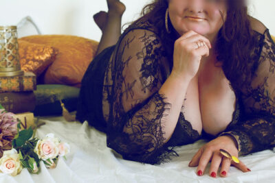 Addison Lane lying on her front, one hand on the floor infront of her, leaning on one elbow, hand on chin, feet bent up in air. Pillows and flowers to one side. Addison Lane wears black lingerie with black lace kimono and has medium length brown hair. NZ Pleasures.