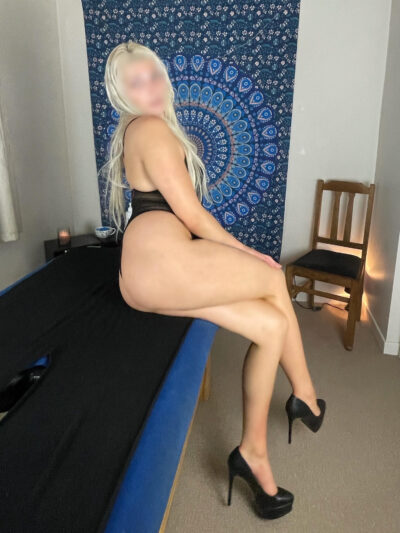 Anna sitting on the edge of a massage table, legs crossed, side on to camera, leaning on one hand, other hand on top of knee, head turned to look at camera. Anna wears a black bodysuit, black heels and has long blonde hair. NZ Pleasures.