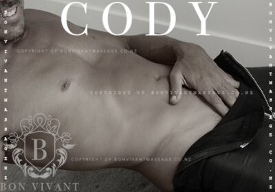 Black and white photo of Cody lying back, leaning on one elbow, the other hand half down the top of his pants, which are unzipped. Cody is topless and wears black pants. NZ Pleasures.