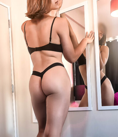 Diana Mojo posing in front of two mirrors on the wall, hands either side of mirror on the wall, one knee bent forward, head to one side. Diana wears black lingerie, her reflection in the mirror and has shoulder length brown hair. NZ Pleasures.