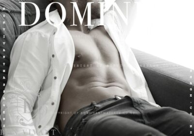 Dominic reclining on a couch, one hand by side of thigh, the other above head, head turned to one side. Dominic wears a white dress shirt that is undone and dblack denim jeans. NZ Pleasures.