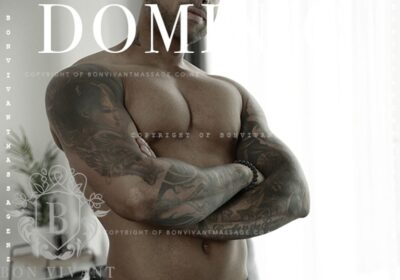 Dominic posing with arms crossed, head titled to one side. Dominic is topless and has tattoos on both arms. NZ Pleasures.