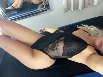 Anna lying on her back on a massage table, back arched, knees bent up. Anna wears a black bodysuit and has long black hair. NZ Pleasures.