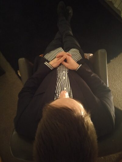 Luke sitting in a chair, hands in laps, legs extended in front of him and crossed at ankles. Photo is taken from behind Luke, and above. Luke wears a black dress jacket, black and white checkered shirt and black pants. NZ Pleasures.