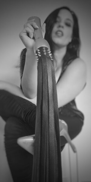 Black and white photo of Mistress V holding a flogger up for the camera. Mistress V is sitting with legs crossed on a stool. NZ pleasures.