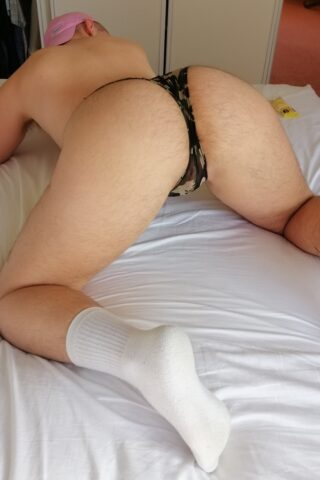 Tommy kneeling on elbows and knees on a bed, knees wide apart, buttocks to camera. Tommy wears beige and brown undies and white socks. NZ Pleasures.