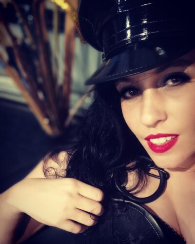 Portrait style photo of Mistress Vivian holding a hat over her chest, smiling at the camera. Mistress Vivian wears a black leather cap and has long black hair. NZ Pleasures.