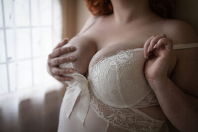 Autumn posing with one hand hooked around the shoulder strap of her bra, her other hand on her breast. Autumn wears white lingerie and has shoulder length auburn hair. NZ Pleasures.