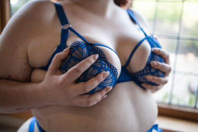 Autumn posing with hands on breasts, photo cropped from shoulders to stomach. Autumn wears blue lingerie. NZ Pleasures.