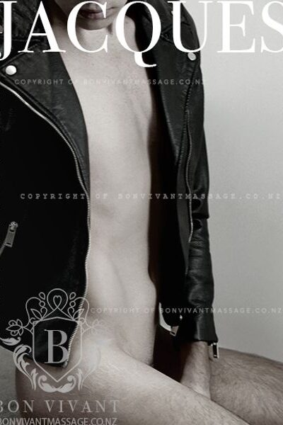 Black and white photo of Jacques kneeling side on to camera, one hand between legs, head titled down. Jacques wears a black leather jacket that is undone. NZ Pleasures.