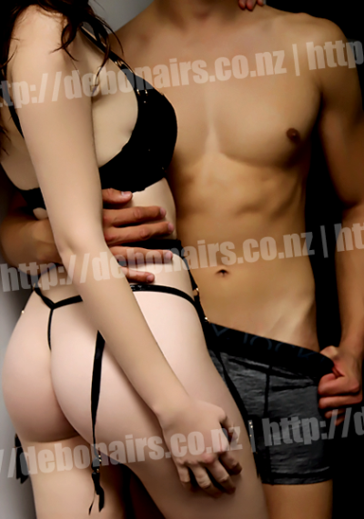 Leo and a woman posing in a half embrace, Leo's hand around the waist of the woman who is turning back to look at camera. Leo has his other thumb pulling down the top of his boxers. Woman wears black lingerie. NZ Pleasures.