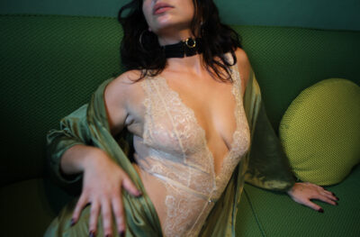 Lilly Idol sitting on a couch, leaning over to one side onto elbow, her body twisted towards camera, hand on hip, head titled back. Lilly wears a cream lace bodysuit, black choker, a satin green dress that is undone and her long hair out. NZ Pleasures.