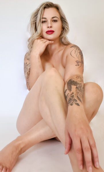 Phoenix sitting of the floor with legs crossed, knees bent up, one arm between legs, hand resting on ankle, the other elbow rests on her thigh, hand under chin. Phoenix is naked except for some tattoos and has long blonde hair. NZ Pleasures.